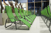 Several green swimming bath sun lounger arranged in a row — Stock Photo