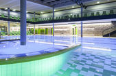 Indoor swimming pool with green interior and illumination — Stock Photo