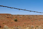 Barbed wire as divider to the hot red desert with blue sky — Stock Photo