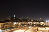 Night panorama of san francisco Coit Tower and a lot of orange busses in the front — Foto de Stock