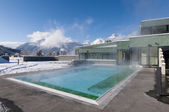 Outdoor pool which is steaming at a cold and clear winter day and mountains in the background — Stock Photo