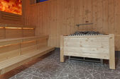 Wooden steam sauna with benches and romantic light — Stock Photo