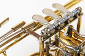 Silver golden trumpet valves in detail view with white background — Stock Photo