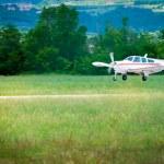 Small sport prop aircraft landing on aspahlt runway — Stock Photo #38768387