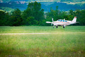 Small sport prop aircraft landing on aspahlt runway — Stock Photo