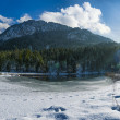 Winter landscape with snow and ice at small lake in front of mountain — Stok fotoğraf