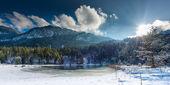 Malé zmrazené jezero v rakouských alpách s slunce svítí přes mraky — Stock fotografie