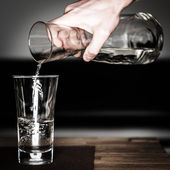 Hand fills in water with glass jug on wooden table — Stock Photo