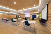 Modern wooden conference room with tables an chairs and projector screen — 图库照片