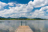Wooden boardwalk into lake hopfen in bavaria at sunny blue summer day — Stockfoto