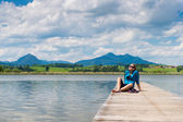 Young woman sitting on pier at lake hopfen with sunny cloudy sky — Stockfoto