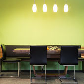 Cantilever chairs at timber table with lamps and green wall — Stock Photo