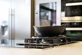 Noodle wok on gas stove on workplate in modern kitchen — Stock Photo