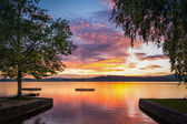 Moody sunset at lake wallersee in austria with trees and wooden platform — Stock Photo