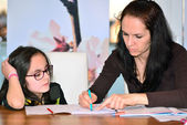 Mother helping girl to do homework — Foto Stock