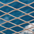 Knitted grid on boat banister — Stock Photo