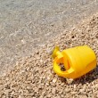 Yellow watering can on the pebbly beach — Stock Photo