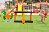 Empty chain swing on modern colorful children playground — Стоковое фото