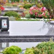 Stock Photo: Flowers and candle on tomb in churchyard