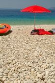 Beach with pebbles and red sunshade on a summer day — Stock Photo