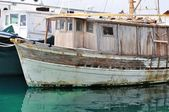 Old abandoned wooden fishing ship on port — Stock Photo