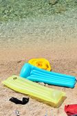 Colorful floating beds with beach items in pebbly beach — Stock Photo