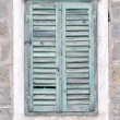 Old window with blue closed shutters on an old house — Stock Photo