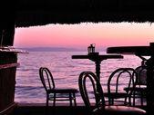 椅子とテーブル熱帯のバーのバーのシルエット — ストック写真
