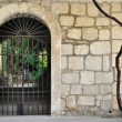 Medieval iron gate in ancient stone wall — Stock Photo #39032989
