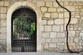 Medieval iron gate in ancient stone wall — Stock Photo