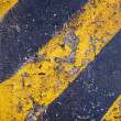 Stock Photo: Yellow and black warning sign on asphalt texture