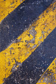 Yellow and black warning sign on asphalt texture — Stok fotoğraf
