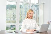 Mujer trabajando con ordenador portátil y escribir notas — Foto de Stock