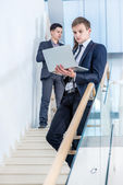 Businessman  holding a laptop on the stairs — Stock Photo
