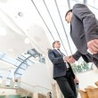 Two young businessmen shake their hands — Stock Photo #47620243