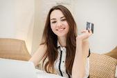 女の子はラップトップで座っていると、オンライン購入を行う — ストック写真