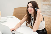 Girl sitting at a laptop and making online purchases — Stock Photo