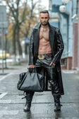 Stylish man with bag in a leather coat. — Zdjęcie stockowe