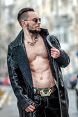 Man in  glasses on the street in a leather coat. — Stok fotoğraf