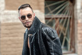 Man on the street in a leather coat. — Stock Photo
