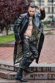 Stylový muž na ulici v koženým kabátem. — Stock fotografie