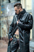 Man in  glasses on the street in a leather coat. — Stockfoto