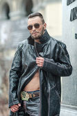 Man in  glasses on the street in a leather coat. — Stock Photo