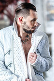 Stylish man with a beard in a white leather coat — Stock Photo