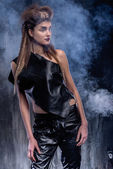 Stylish woman in a leather dress standing in smoke. — Stock Photo