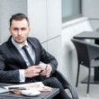 Thoughtfulness. Young businessman holding a cup of coffee in han — Stock Photo #47834769