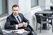 Thoughtfulness. Young businessman holding a cup of coffee in han — Stock Photo
