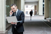 Businessman talking on the phone and  holding a laptop — Stock Photo