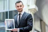Businessman shows the tablet in camera — Stock Photo