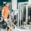 Strength training in the gym. Two young men are engaged in sport — Stock Photo #47955959